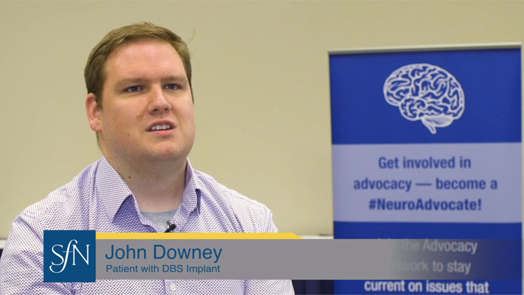 Image of John Downey wearing a lavender button down shirt speaking to the camera about deep brain stimulation.