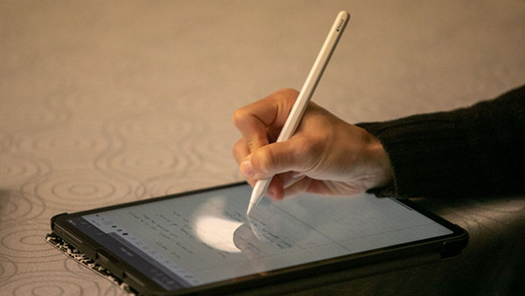Image of someone's hand writing with a stylus on a tablet.