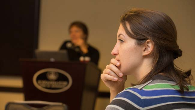 A female listens intently to a presentation.