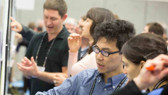 Male and female neuroscientists discuss scientific posters at SfN's annual meeting.