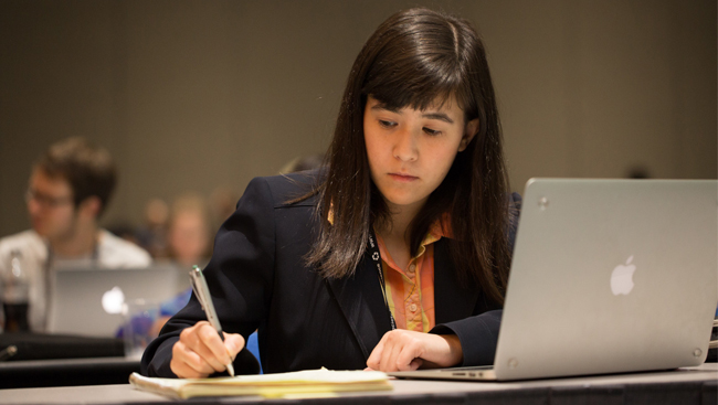 Young Woman in Business Attire with Laptop Open Taking Notes During Lecture
