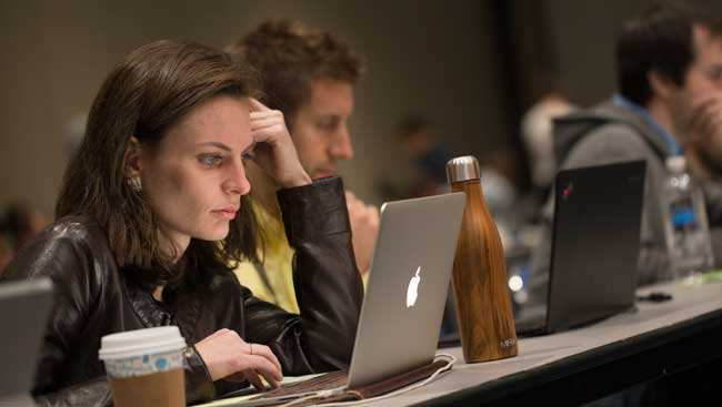 Woman Focused on Laptop in Lecture Hall