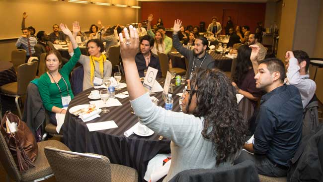 Room of Seated Men and Women Raising their Hands at an Event