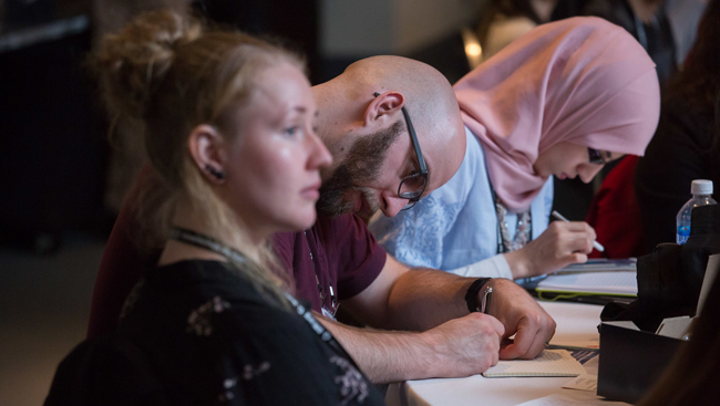 Neuroscience 2017 attendees taking notes at a table