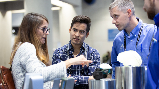 Three people discussing a product on the exhibit floor at Neuroscience 2018.