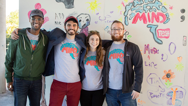 The primary members of the MIND Coalition, including cofounders Stallmann and Lovan, stand in front of an art wall at MINDfest 2018 that invited attendees to paint what mental health means to them. From left to right: Nathan Jones, Bradford Martins, Rebecca Stallmann, and Elijah Lovan.