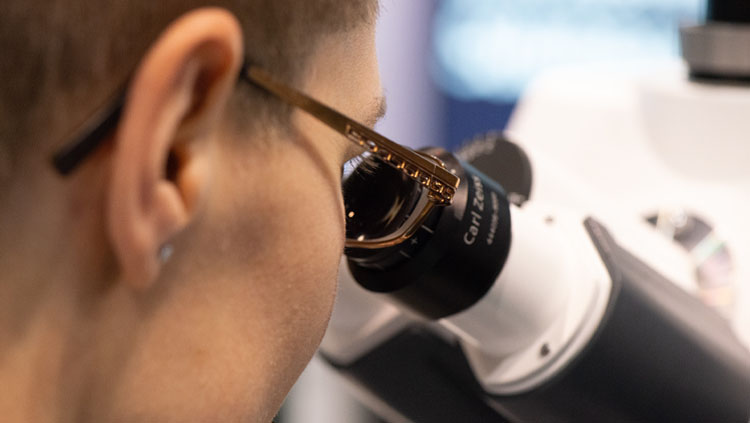 A close up of a person wearing glasses looking into a microscope.