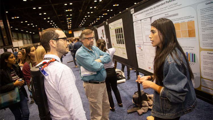 Two men listening to a woman explain her poster presentation at Neuroscience 2019.