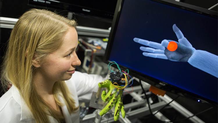 PhD student Karen Schroeder demonstrates a task in monkeys, in which they control animated finger movements with bend sensors on their fingers. Photo credit: College of Engineering, University of Michigan.