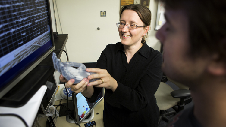 Cynthia Chestek talking to a PhD student while holding the Touch Bionics multi-articulated prosthetic hand.