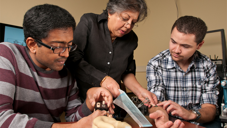 Jung discussing with Sathyakumar Kuntaegowdanahalli (left, research engineer) and Andres Pena (right, doctoral graduate student) the functioning of components of the ANS-Neural-Enabled Prosthetic Hand system: myoelectric control by the user of the prosthetic hand, and electronics for processing information from force and hand opening sensors embedded in the prosthetic hand. Courtesy of the Adaptive Neural Systems Laboratory, Florida International University.