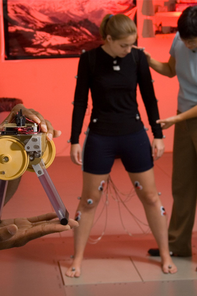 A small biomimetic robot, designed to test understanding of how the nervous system controls balance while a former PhD student in the Neuromechanics Lab, Stacie Chvatal, stands on two force plates. She is instrumented with electrodes on the skin.