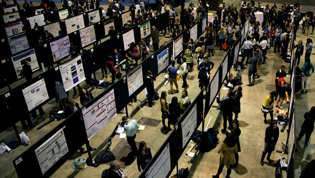 Male and female neuroscientists present their research findings at a conference.
