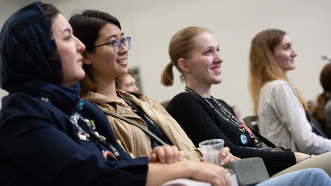 An image of four female neuroscience 2018 attendees smiling during a panel session