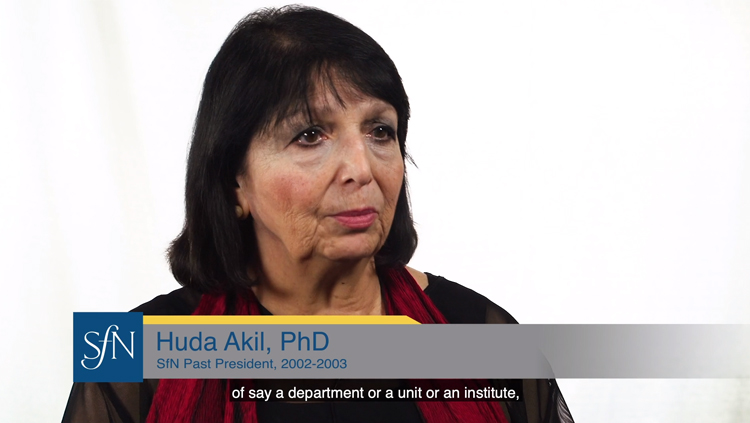Huda Akil sits in front of a white backdrop and speaks about the importance of gender parity.
