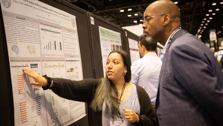 Image of a young woman explaining her poster presentation to a man at Neuroscience 2019.