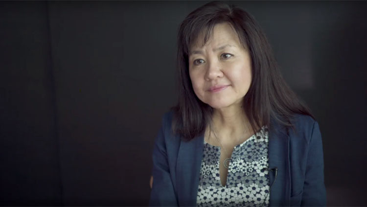 Li-Huei Tsai sitting in front of a gray background during an interview.