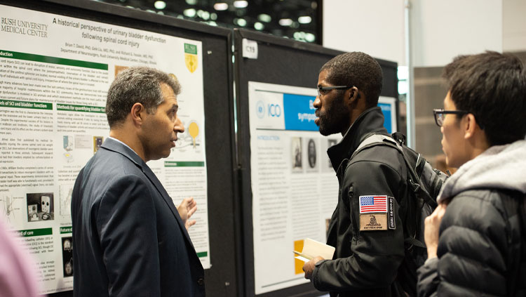 Three people discuss a poster at neuroscience 2019.