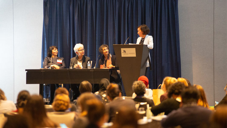 Three panelists sit at a table while a moderator stands at a podium at the celebration of women in neuroscience luncheon 2019