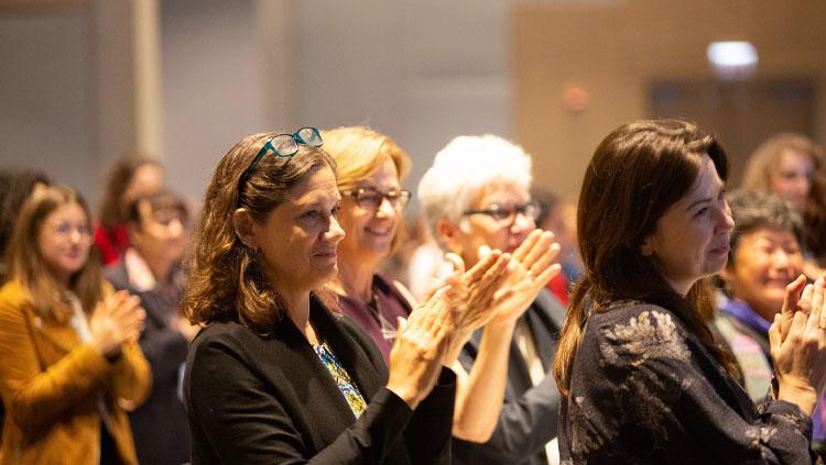 Women sit in rows applauding a speaker.