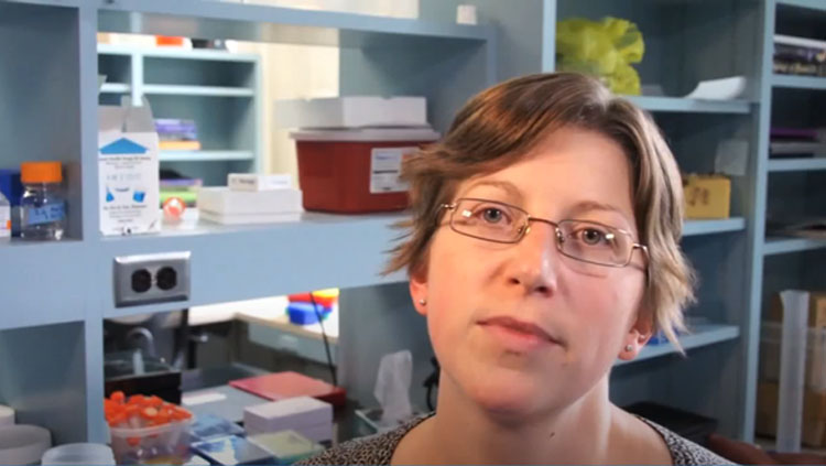A woman wearing glasses speaks to the camera.