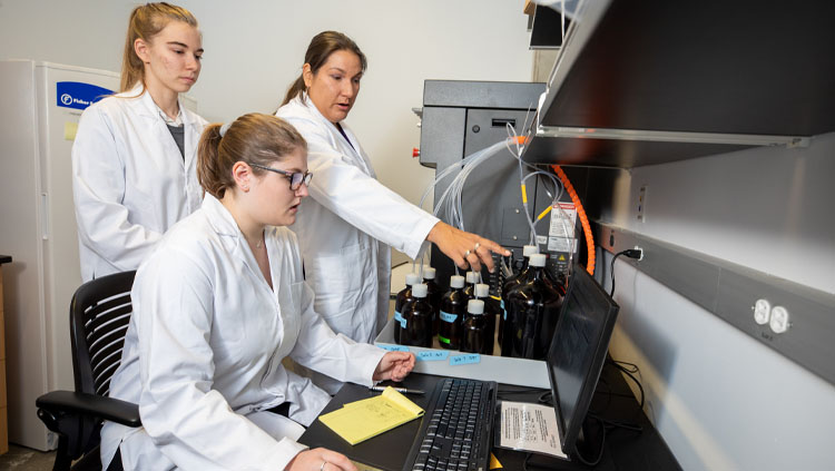 Naomi Lee instructs Jasmyn Genchev (BS, Chemistry, 2022) and Noelle Waltenburg (BS, Chemistry, 2020) how to use the Prelude X peptide synthesizer from Gyros Protein Technologies. Photo taken by NAU Marketing.