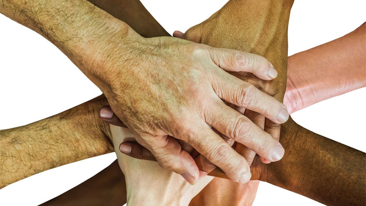 Several hands piled on top of each other to signify unity.
