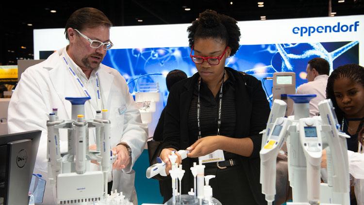 A man in a lab coat walks a woman through an instrument demonstration at Neuroscience 2019.