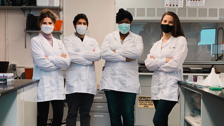 Four scientists stand in front of their lab benches wearing lab coats with their arms crossed.
