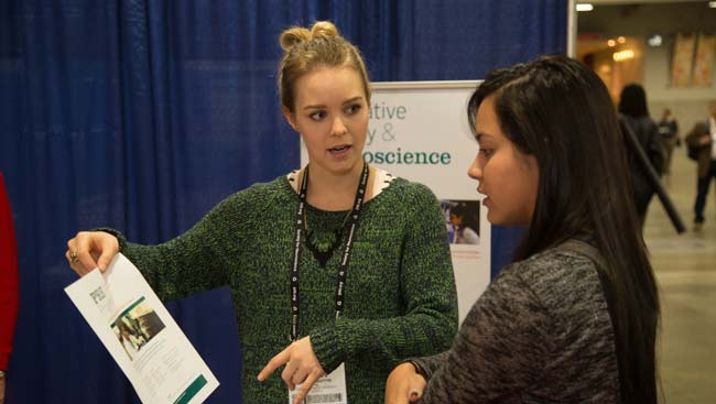 Two women discuss the contents of a piece of paper at the SfN Annual Meeting.