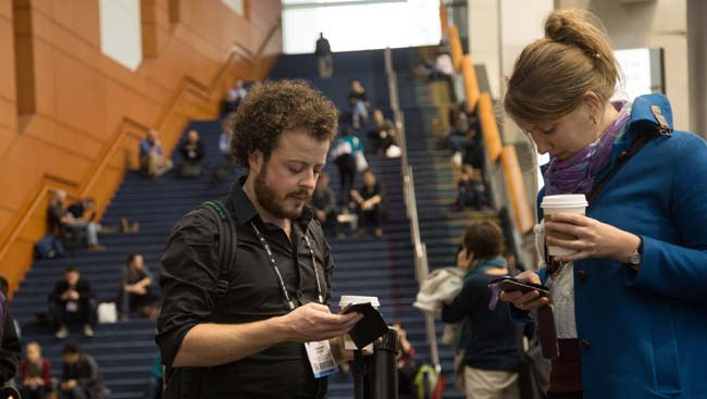 Male and female conference attendees share tweets at the annual meeting.