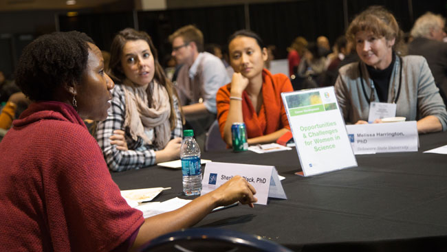 A group of female neuroscientists discuss career development while sitting at a table.