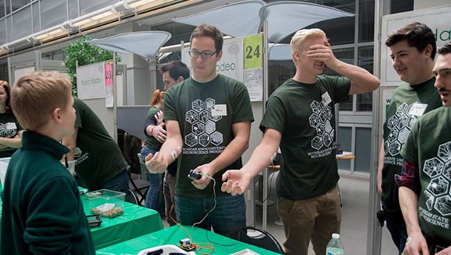 Male neuroscientists interact with children at an outreach event.