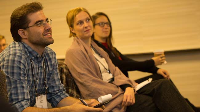three neuroscientists sit listening to a lecture.