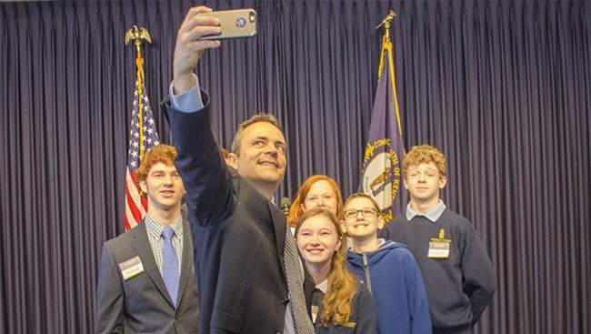 Lawmaker takes photo with a group of students.