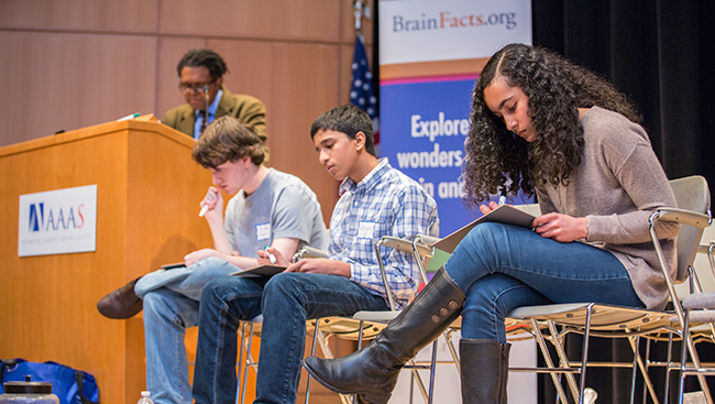 Three students sit on a stage to participate in a presentation