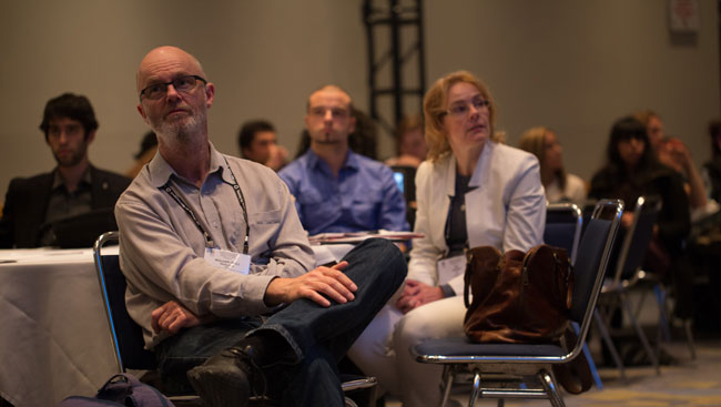 Neuroscientists sit listening to a lecture.