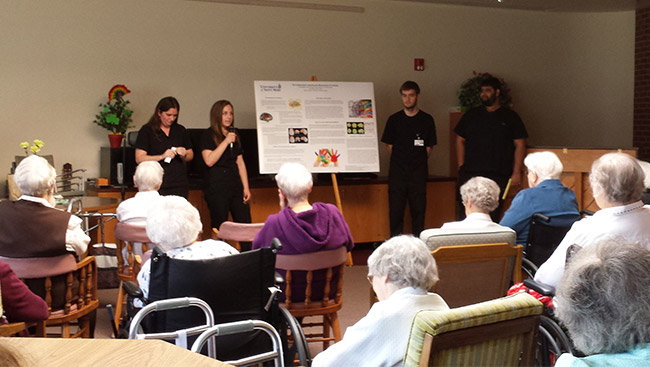Male and female neuroscience students give a presentation on healthy brain habits to the community.