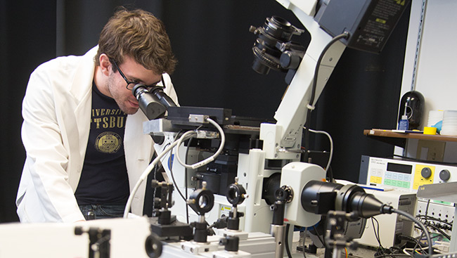 A male neuroscientist uses lab equipment to conduct research.