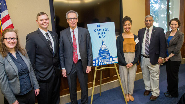 Neuroscientists stand around a sign for a picture at SfN's Capitol Hill Day