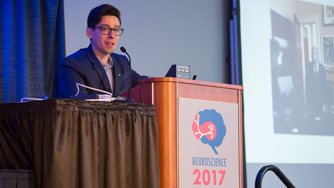Michael Wells gives a speech standing at a podium at Neuroscience 2017.