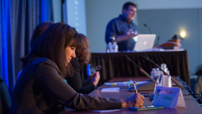 Panelists listen as a man speaks at the podium during the Animals in Research panel from Neuroscience 2017