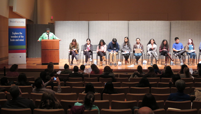 Image of several students sitting on stage during 2017 DC Brain Bee stage.