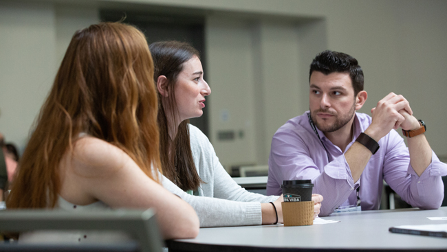"Photo of three attendees having a discussion during the Professional Development Workshop, ""Bringing a Student-Run Outreach Program to Your Institution"""