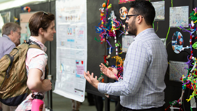 Poster presenter discussing research  with an attendee at Neuroscience 2018