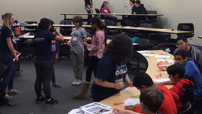 With the help of Carnegie Mellon Nu Rho Psi members, middle school students play partner games and cut out parts of pictures to learn about reflexes and optical illusions.