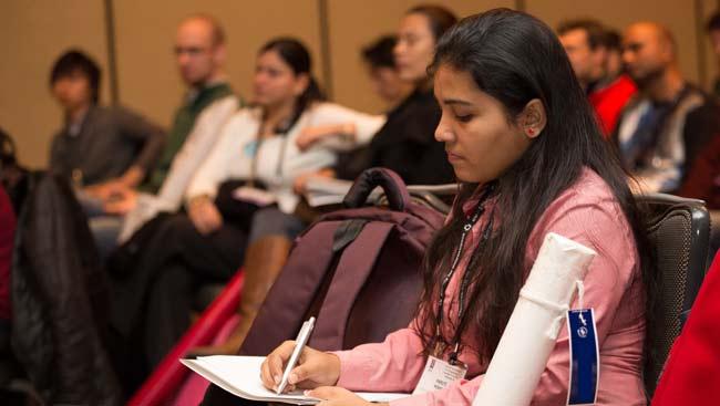 A female neuroscientist takes notes during a talk.
