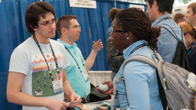 A male and female student network at a graduate school fair.