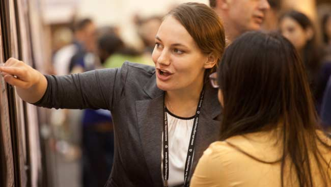 Female neuroscientist points to a scientific poster as she talks with another female neuroscientist at SfN's annual meeting.