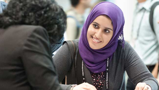 Young woman smiling and talking with another woman at SfN's annual meeting.